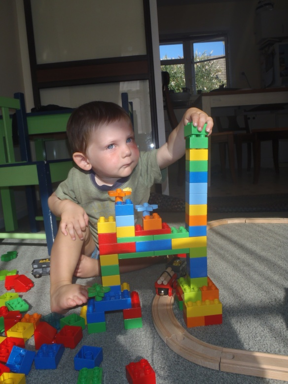 Building a tower is serious business. Mama helped get the bridge structure going (since Daddy wasn't home yet), and I embellished it with flowers and a tall asymmetrical tower.